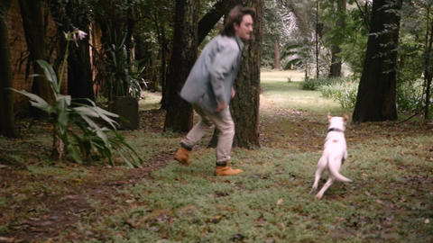 A handsome man playing with his dog while she runs very fast by him in a game of Footage