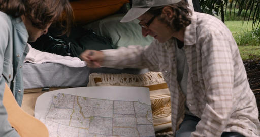 Two men planning their road trip in the USA looking and pointing at a paper map Footage
