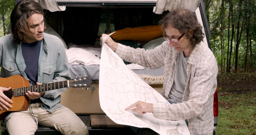 Man looking at a paper map while his male friend plays guitar while camping and Footage