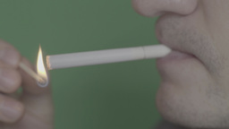 A cigarette light it and smoke on a green background Footage