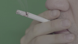 Closeup of cigarette in the smoker's mouth on a green background Footage