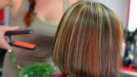 Hairdresser who combs hair done in colored stripes and stretch it with a plaque  Footage