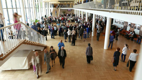 People crowd in concert hall lobby room, round in circle, some dance in middle Footage