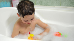 Boy playing with ducks in water covered with foam in the bath tub 9 Footage