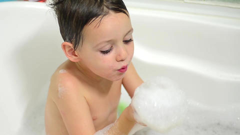 Boy plays foam which keeps in hand while bathing in tub 1 Footage