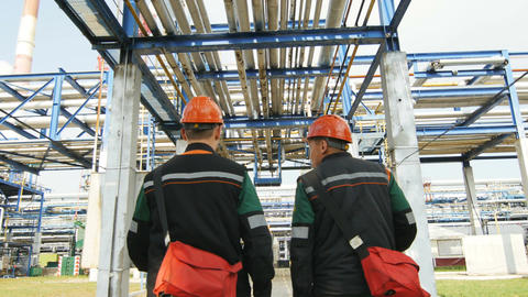 Backside View Workers Walk along Gas and Oil Refinery Plant Footage