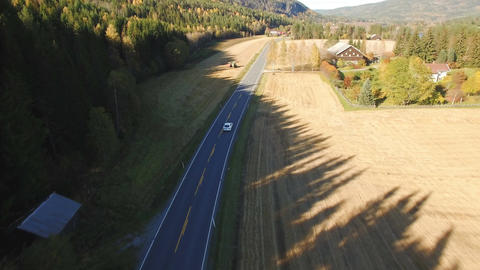 White car driving on a country road among the woods and fields of Norway Footage