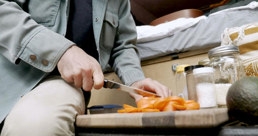 Pan up of a handsome hipster millennial man preparing food while camping in his Footage