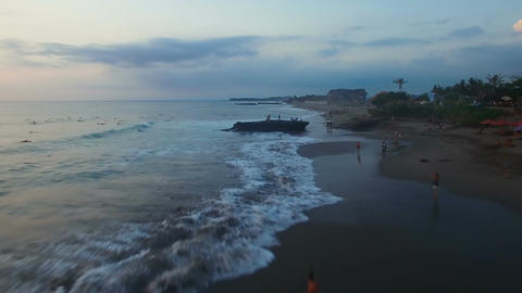 Ocean beach with surfers and tourists at sunset aerial Footage