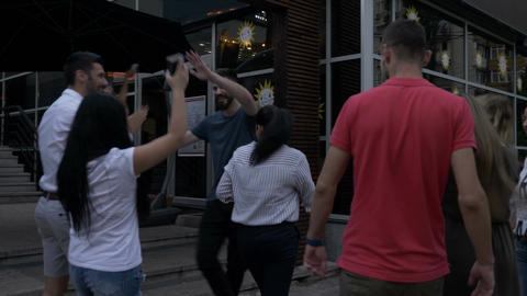 Group of happy friends meeting in front of the club and enter the party hanging Footage