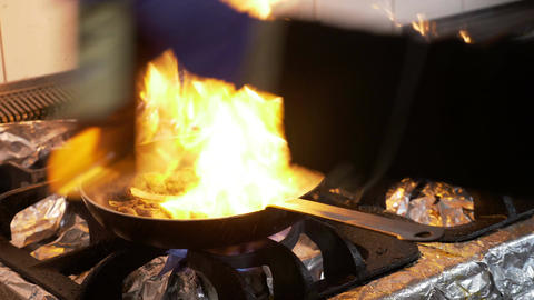 Closeup of stove with pan and chef cooking adding olive oil and flaming the Footage