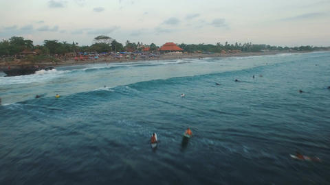 Aerial footage of surfers in ocean waiting for the big wave in evening Footage
