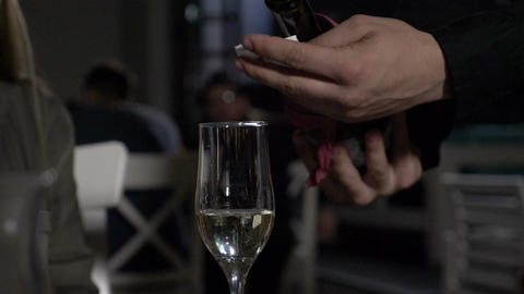 Slow motion of champagne poured in glass by waiter in a fancy restaurant Footage