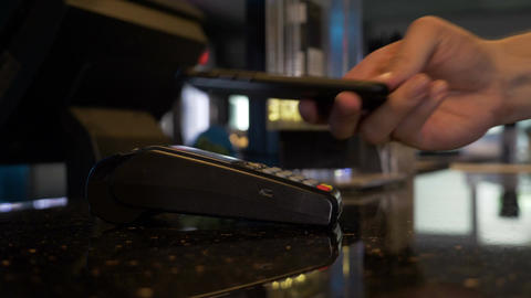 Closeup of man paying with bitcoin contactless with smartphone and terminal pos Footage