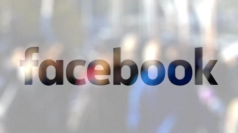 Facebook logo on a glass against blurred crowd on the steet. Editorial 3D Live Action