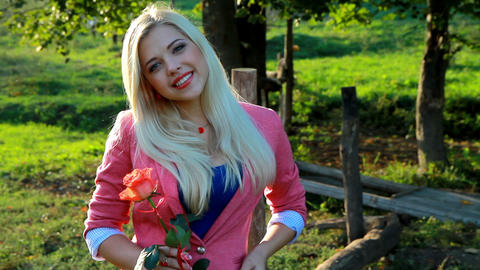 Smiling young lady holding a red rose Stock Video Footage
