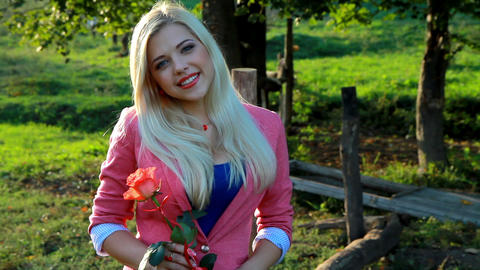 Smiling young lady holding a red rose Footage
