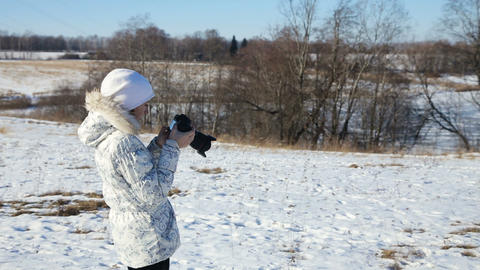 Girl in winter park with camera photographs Footage