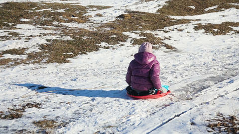 Little girl sledging down hill Footage