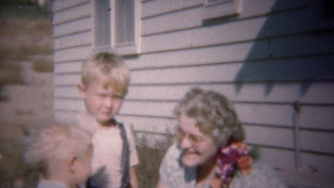 1949: Blonde baby brothers playing with grandma with corsage Footage