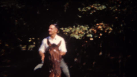 1943: Dapper man casually riding brown horse in autumn sunshine Footage