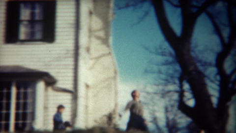 1947: Man running past white mansion house throwing stick for dog Footage