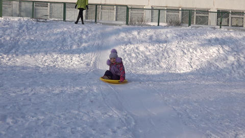 Child Ride on a Plate on Hill, Kid Sledding in Winter Footage