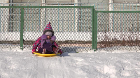 Child Ride on a Plate on Hill, Kid Sledding in Winter. 4K UltraHD, UHD Footage