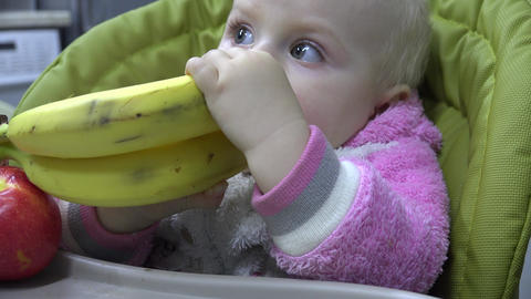 Cute Baby Eating an Banana, First Teeth. First Try to Chewing. 4K UltraHD, UHD Footage