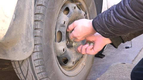 Mechanic Hands Replace Car Tire Outdoor. Closeup. 4K UltraHD, UHD Footage