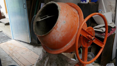 Man pours a substance into a concrete mixer Footage