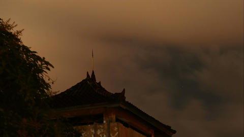 Stars and clouds above temple roof in Indonesia, time lapse Footage