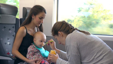 Two Young Ladies Feeding a Baby on the Train Footage