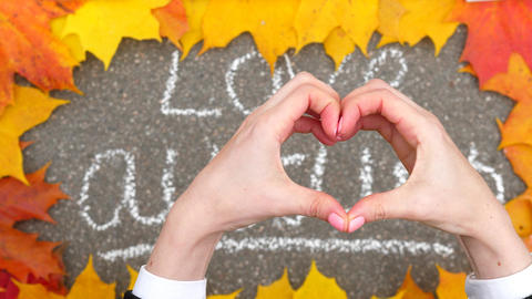 Woman hold hands in shape of heart against chalk written 'love autumn' GIF