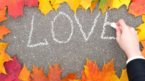 Woman write LOVE on asphalt using white chalk, colourful maple leaves frame Live Action