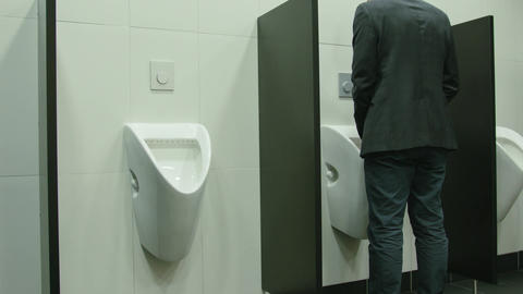 Man Peeing to Urinal in the Restroom Archivo