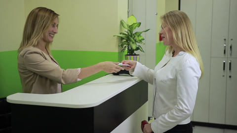 Happy woman paying with credit card at spa salon Image