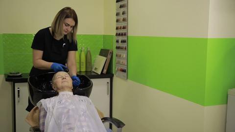 Senior woman getting hair wash procedure in salon Live Action