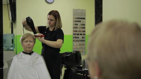 Hairdresser drying female customer's hair in salon Live Action