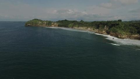 Aerial shot of ocean waves crashing coastline cliff Footage
