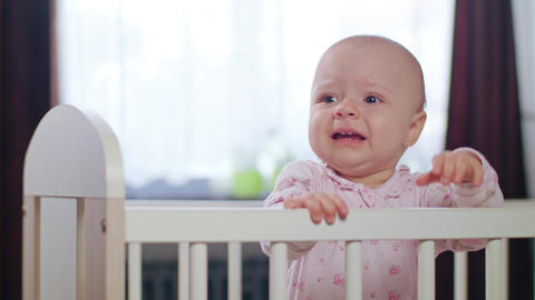 Baby Standing in a Crib at Home. Crying Footage