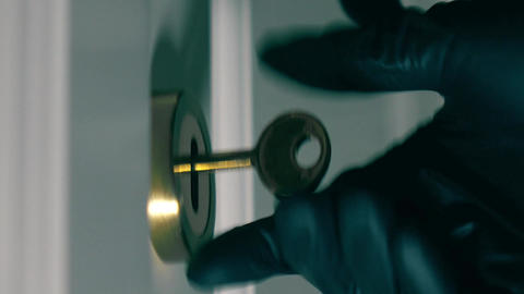 Person wearing black gloves opens locked door with a key Footage