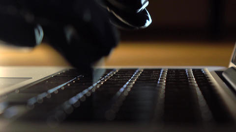 Person wearing black gloves typing on laptop keyboard and using touchpad Footage