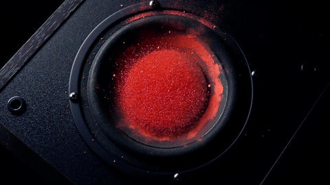 Shaking subwoofer throws orange dust in the air Live Action