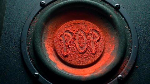 Pop inscription on orange powder over trembling speaker Footage