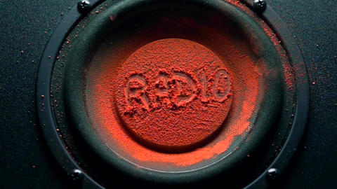 Radio inscription on orange powder over trembling loudspeaker Live Action