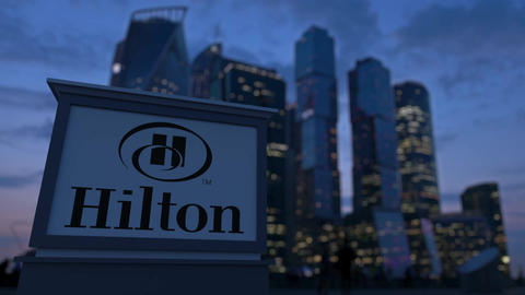 Street signage board with Hilton Hotels Resorts logo in the evening. Blurre Footage
