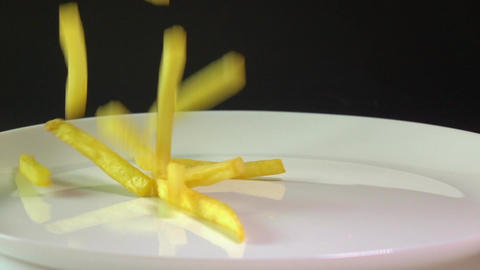 Pouring golden french fries on the plate. Popular fast…, Live Action