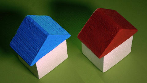 Man and woman picking toy houses against green background. Real estate market Footage