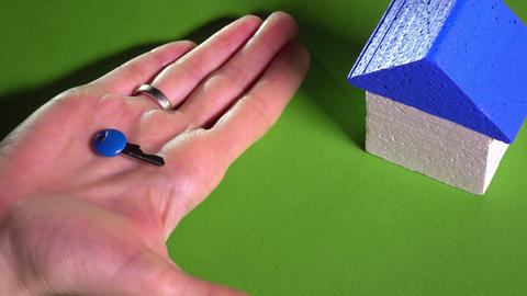 Realtor placing toy house with blue roof and holding small key against green Footage
